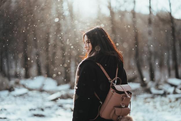 Modelo hermoso joven que presenta en bosque del invierno. elegante retrato de moda Foto gratis
