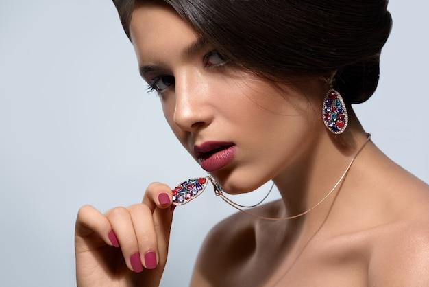 Modelo de moda joven que luce con fiereza y confianza con aretes y un collar con piedras preciosas multicolores Foto Premium