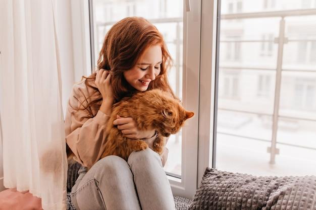 Modelo de mujer agradable con gato rojo de rodillas. retrato de interior de encantadora mujer jengibre posando con mascota. Foto gratis