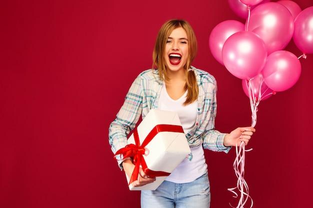 Modelo de mujer celebrando y sosteniendo caja con regalo presente y globos rosados Foto gratis