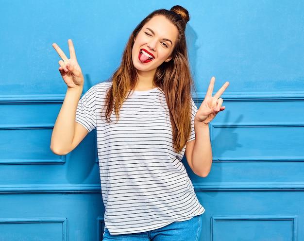 Modelo de mujer joven y elegante en ropa casual de verano con labios rojos, posando junto a la pared azul. guiñando un ojo y mostrando el signo de la paz Foto gratis