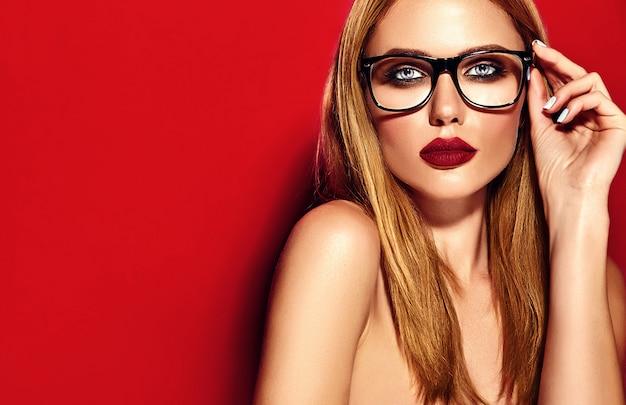 Modelo de mujer rubia hermosa caliente con maquillaje diario fresco con color de labios oscuros y piel limpia y sana sobre fondo rojo en gafas Foto gratis