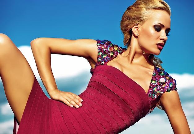 Modelo de mujer rubia sexy joven en vestido rojo de noche posando sobre fondo de cielo azul Foto gratis