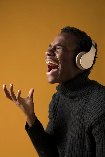 Modelo negro cantando con cascos Foto gratis