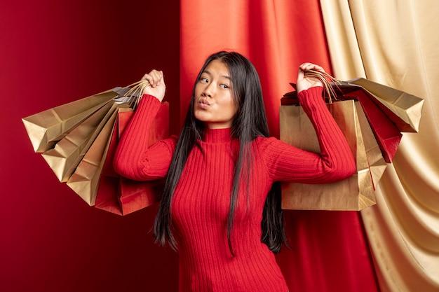 Modelo posando con bolsas de papel para año nuevo chino Foto gratis