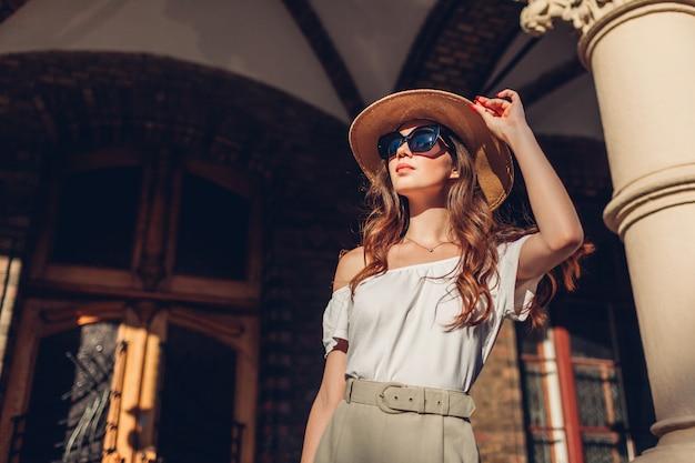 Modelo. retrato al aire libre de la mujer turística que disfruta de hacer turismo en lviv. niña mirando la arquitectura antigua Foto Premium