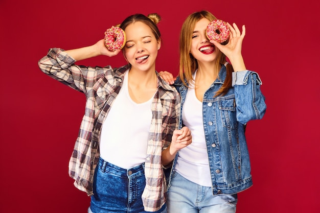 Modelos femeninos con rosquillas rosas con chispas Foto gratis