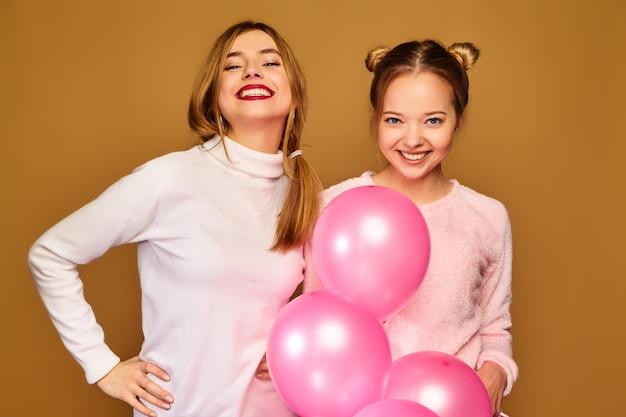 Modelos de mujeres con globos rosados en la pared dorada Foto gratis
