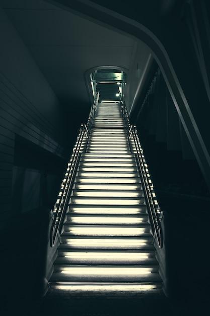 Modernas escaleras de piedra gris industrial iluminadas con luces que conducen Foto gratis