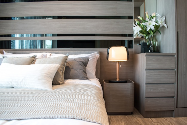 Moderno diseño interior del dormitorio con almohadas de rayas marrones y grises. Foto Premium