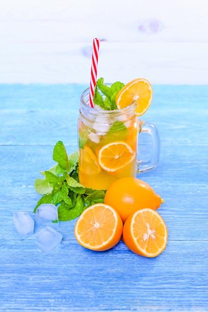 Mojito cóctel de verano con menta, jugo de limón, agua de soda y hielo sobre una mesa blanca de madera azul. Foto Premium