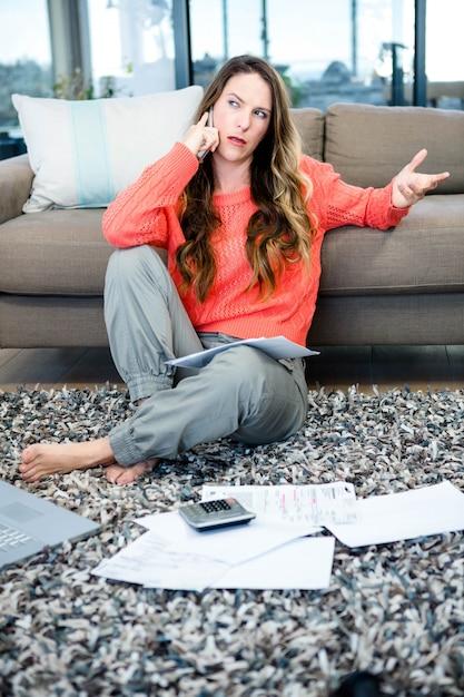 Molesta mujer sentada en el suelo haciendo una llamada telefónica Foto Premium