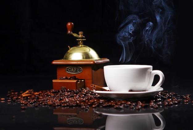Molino de café sobre la mesa con granos de café alrededor Foto gratis