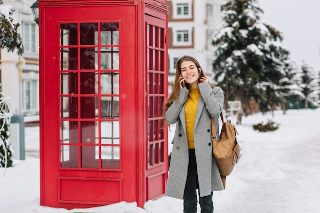 Momentos felices del invierno de la mujer joven de moda alegre que habla por teléfono en la calle cerca de la cabina del teléfono rojo. clima helado de invierno, tiempo de nieve, emociones verdaderas positivas, sonriendo. lugar para el texto. Foto gratis