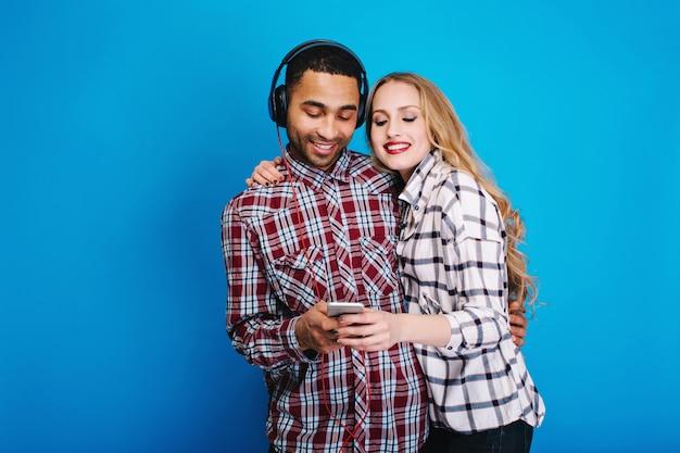 Momentos felices de pareja alegre escuchando música. divertirse, usar el teléfono, hobby, fines de semana, tiempo libre, disfrutar canciones, expresar positividad, sonreír, amantes. Foto gratis