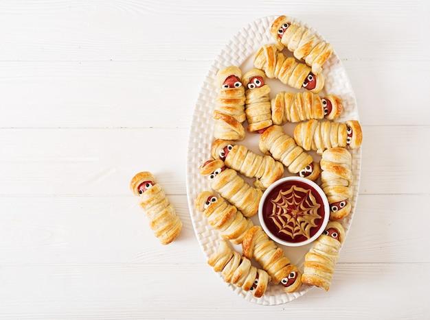 Momias de salchicha aterradora en masa con ojos divertidos en la mesa. decoración graciosa comida de halloween vista superior. lay flat Foto Premium