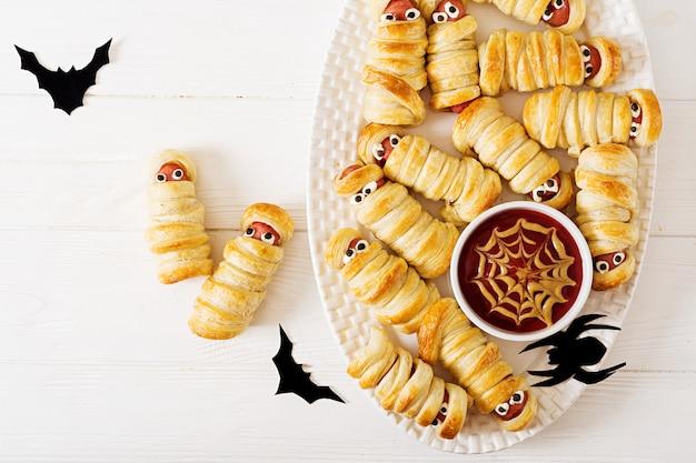Momias de salchicha aterradora en masa con ojos graciosos en la mesa. decoración divertida comida de halloween vista superior. lay flat Foto Premium