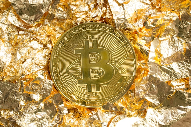 Moneda de bitcoin en piezas de lámina dorada alrededor de fondo decorativo Foto gratis