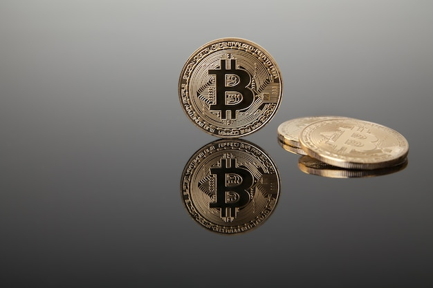 Moneda criptográfica. bitcoins de oro sobre vidrio gris con reflejo Foto Premium