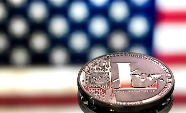 Moneda de litecoin sobre un fondo de bandera estadounidense, el concepto de dinero virtual, primer plano. Foto gratis