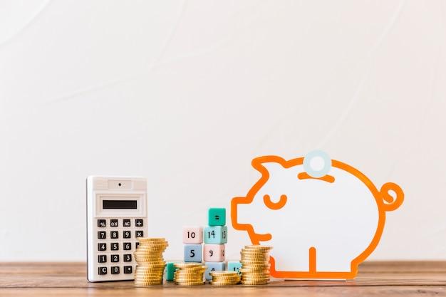 Monedas apiladas, bloques de matemáticas, calculadora y alcancía en la mesa de madera Foto gratis