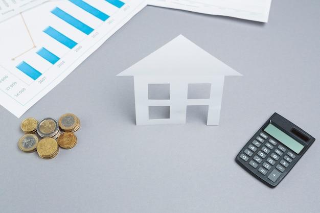 Monedas apiladas y recorte de papel de la casa con la calculadora en el escritorio de negocios Foto gratis