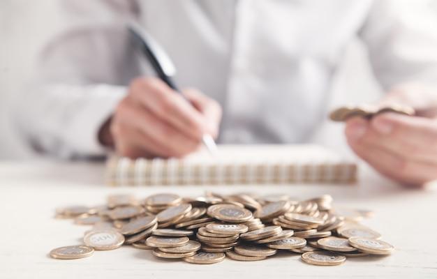 Monedas en el escritorio. hombre contando monedas y escribiendo en el bloc  de notas   Foto Premium
