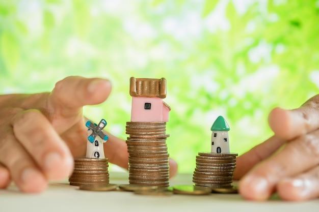 Monedas mimadas a mano y modelo de casa pequeña Foto gratis