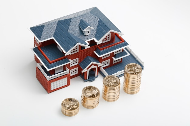 Monedas rmb apiladas en frente del modelo de vivienda (precios de la vivienda, compra de vivienda, bienes raíces, concepto de hipoteca) Foto gratis
