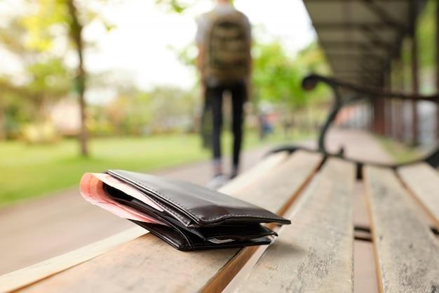 Monedero de cuero con un dinero en el banco del parque mientras los turistas se alejan. - imagen Foto Premium