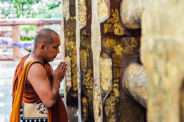 Monje budista indio que se coloca y que ruega delante del árbol de bodhi cerca del templo de mahabodhi en bodh gaya, bihar, la india. Foto Premium