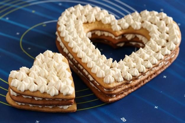 Montaje de pasteles en forma de corazón con crema de mantequilla Foto Premium