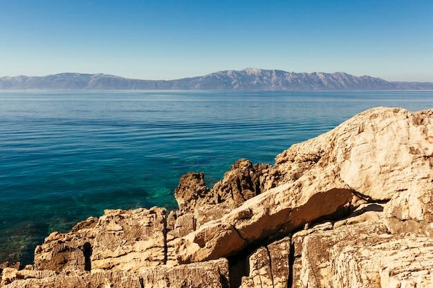 Montaña rocosa cerca del hermoso lago Foto gratis
