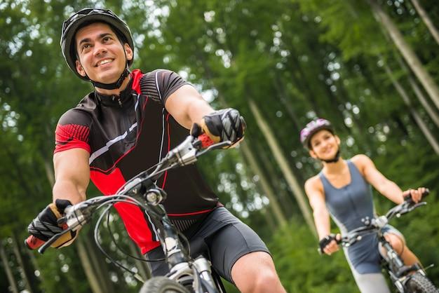 Montar a caballo deportivo joven de los pares en las bicicletas en el camino forestal. Foto Premium