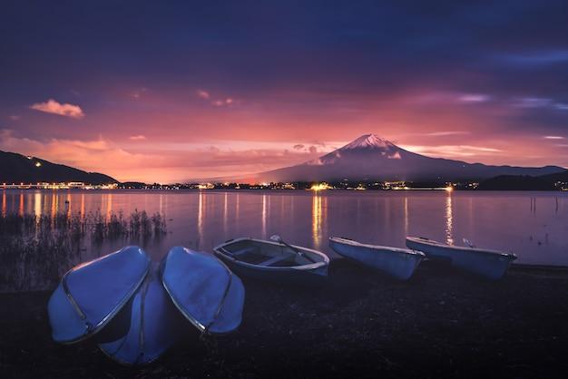 Monte fuji sobre el lago kawaguchiko con barcos al atardecer en fujikawaguchiko, japón. Foto Premium