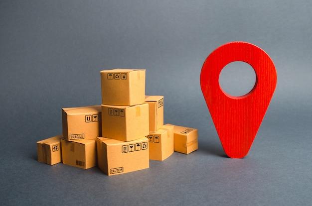 Un montón de cajas de cartón y un pin de posición rojo. localización de paquetes y mercancías. Foto Premium