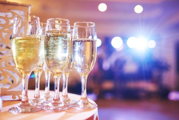 Un montón de copas de vino en la luz azul con un delicioso champán o vino blanco en el bar. Foto gratis