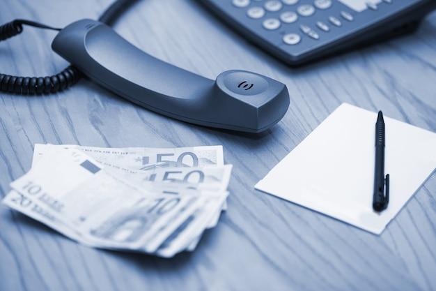 Montón de dinero en la mesa de oficina y teléfono Foto gratis