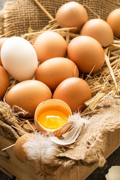 Montón de huevos marrones frescos en una caja de madera Foto Premium
