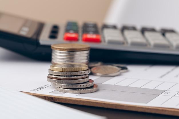 Montón de monedas de dinero con papel cuadriculado en mesa de madera, concepto en cuenta, finanzas y crecimiento del negocio Foto Premium