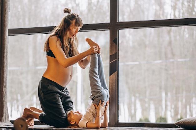 Mopther embarazada haciendo yoga con su pequeña hija Foto gratis