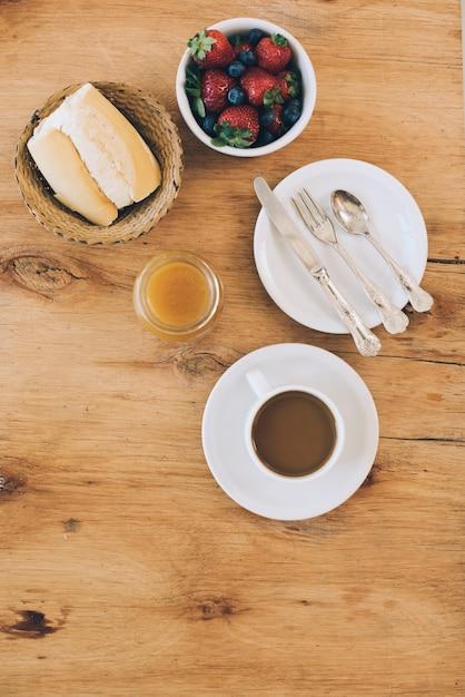 Moras frecas; un pan; taza de mermelada y café sobre fondo con textura de madera Foto gratis