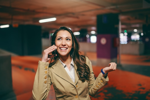 Morena caucásica sonriente vestida elegante usando un teléfono inteligente y mirando hacia el estacionamiento subterráneo. Foto Premium