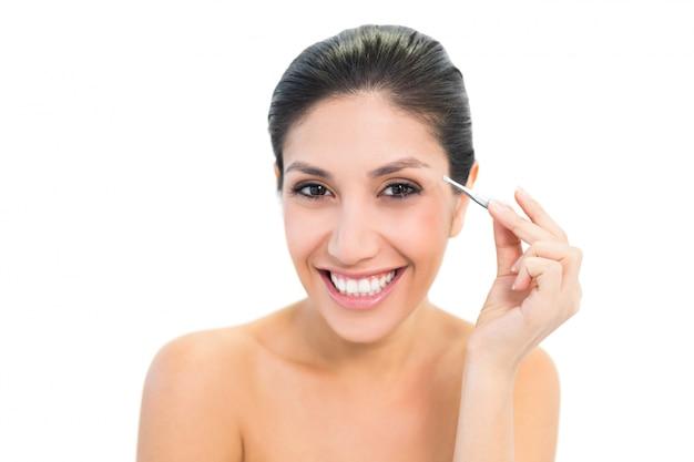 Morena depilando sus cejas y sonriendo a la cámara Foto Premium
