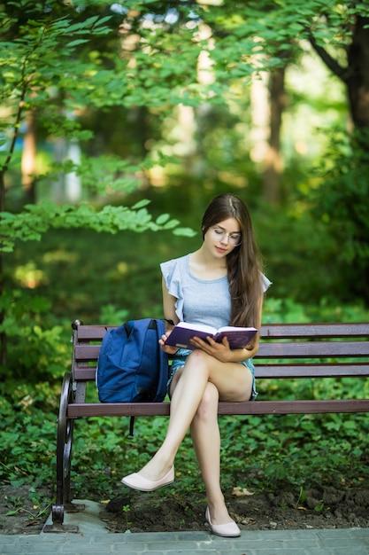 Morena feliz con un cuaderno en las manos sentado en un banco del parque Foto gratis