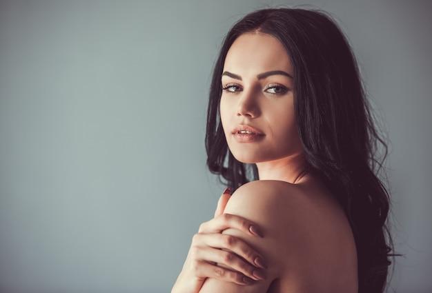 Morena con hombros desnudos mirando sensualmente a la cámara. Foto Premium