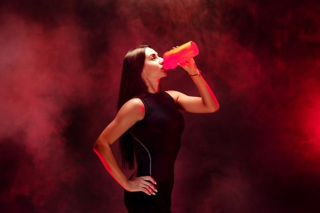 Morena sexy con cabello muy largo y aspecto deportivo posando Foto Premium