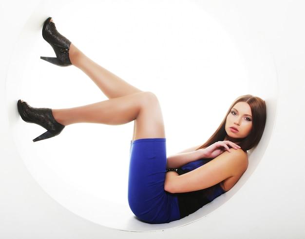 Morena con vestido azul sentada en un círculo Foto Premium