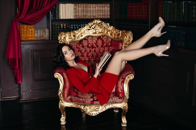 Morenita joven atractiva que miente en el sillón grande en biblioteca. Foto Premium