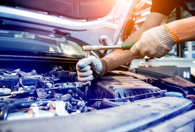 Motor de reparación de mecánico de automóviles en la estación de servicio. reparación de autos. Foto Premium